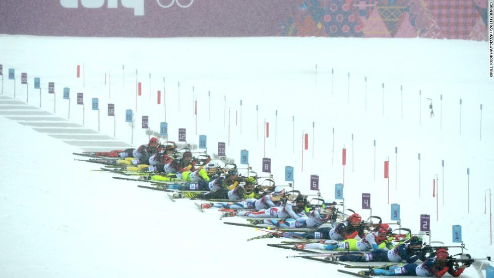Biathletes compete at the firing range in the men's 15-kilometer mass start.