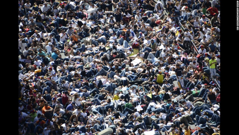 Thousands of students lie on the ground during a protest in front of the Venezuelan Judiciary building in Caracas on February 15.