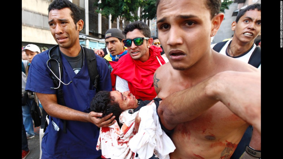 The body of a protester is carried away after gunshots were fired during an anti-government rally in Caracas on February 12.