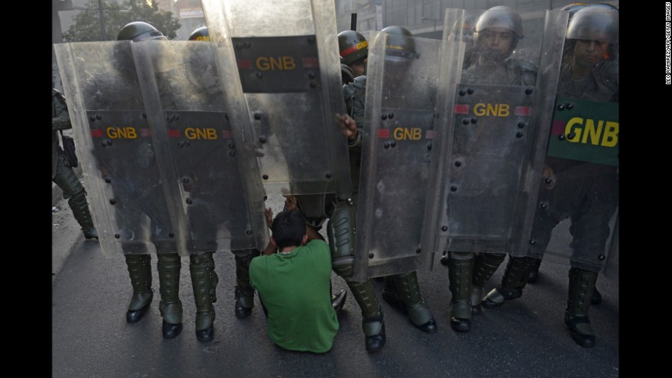 A student falls to the ground in front of riot police in Caracas on February 12.
