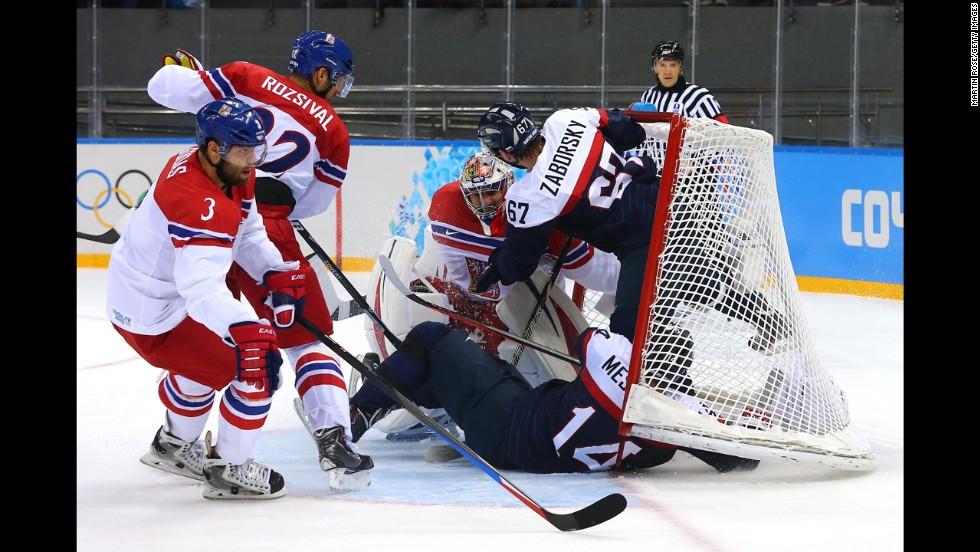 Slovakian hockey players Andrej Meszaros and Tomas Zaborksy crash into Czech goalie Ondrej Pavelec on February 18.