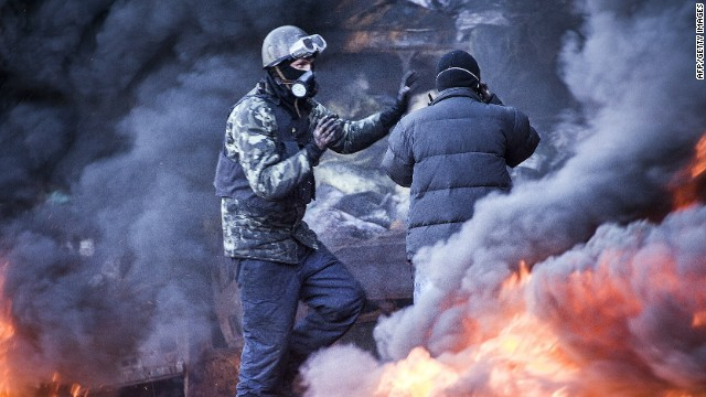 Anti-government demonstrators stand among the smoke of burning barricades during clashes with riot police in Kiev on February 18, 2014.