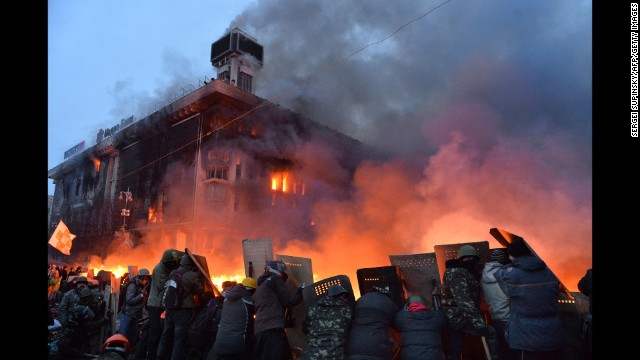 Protesters protect themselves behind shields as they clash with the police in Kiev on February 19.