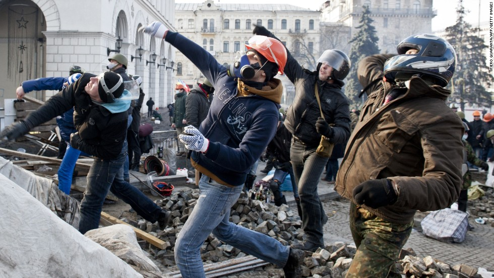 Protesters throw rocks at riot police in Independence Square on February 19.