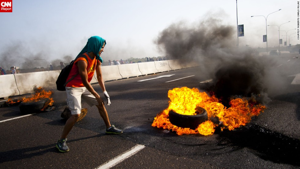 "A student in Maracaibo <a href=""http://ireport.cnn.com/docs/DOC-1086131"">lights a tire on fire</a> on February 15. Rojas explained this is a maneuver students use to close down streets."