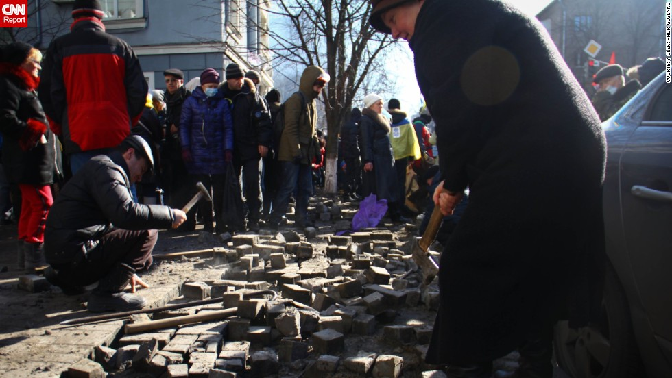 "A woman on a Kiev street digs up pavement bricks to be used as weapons by pro-Europe demonstrators. Ukrainian student <a href=""http://ireport.cnn.com/docs/DOC-1087308"">Oleksandr Guzenko</a> said he was fascinated by ""how motivated and brave [protesters] were to stand there and make a change, support and contribute."""