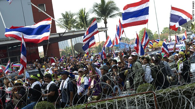 Thai anti-government protesters wave national flags outside the government's temporary office in the permanent secretary for defence suburb of Bangkok on February 19, 2014. Defiant Thai opposition protesters threatened to storm Prime Minister Yingluck Shinawatra's crisis headquarters on February 19, stepping up their campaign a day after dramatic street clashes left five dead and dozens wounded. AFP PHOTO / PORNCHAI KITTIWONGSAKULPORNCHAI KITTIWONGSAKUL/AFP/Getty Images