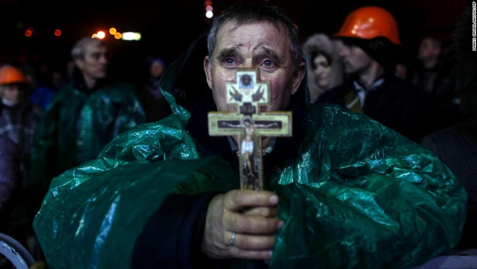 Un manifestante sostiene un crucifijo mientras ora en la Plaza de la Independencia.