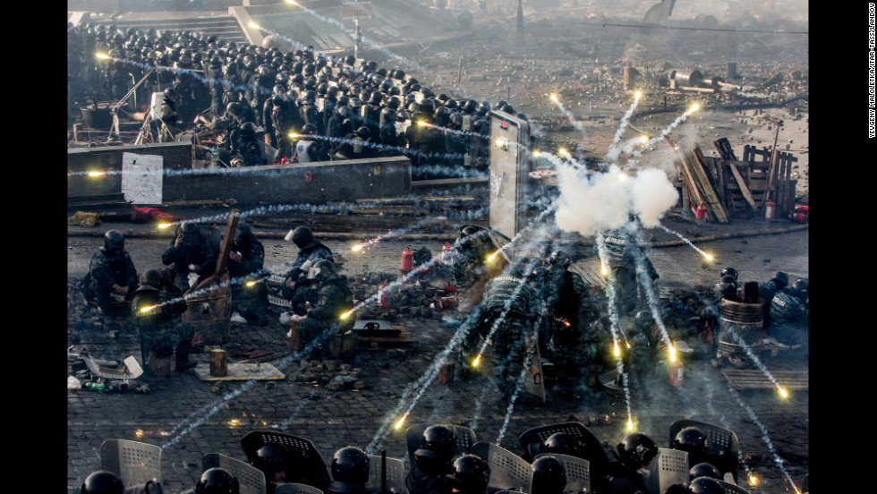 Police take cover behind shields as fireworks go off in Kiev on February 19.