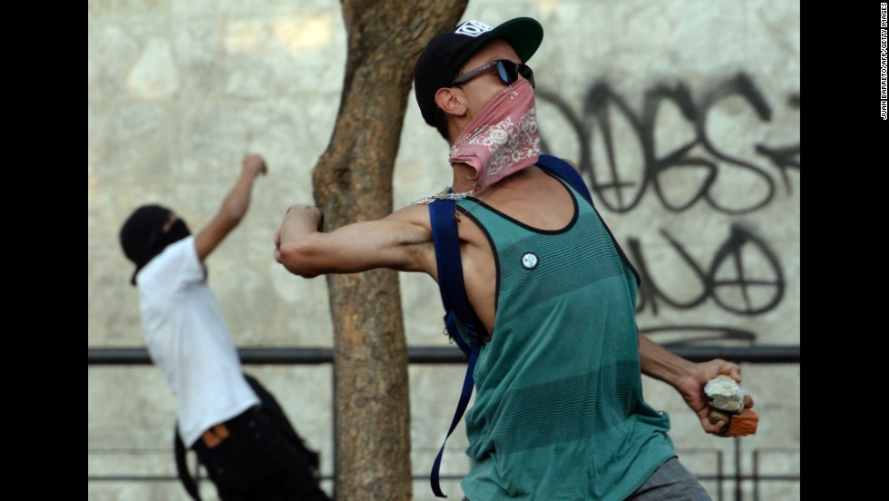 Protesters throw stones at riot police in Caracas on February 19. Protesters have been demanding better security, an end to scarcities, and protected freedom of speech.