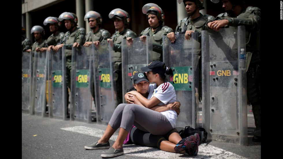 Two women sit in front of a line of National Guard officers outside the Palace of Justice in Caracas on February 19.