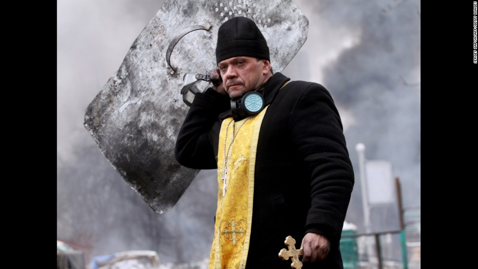 A priest walks with a cross and shield during clashes in central Kiev on February 20.