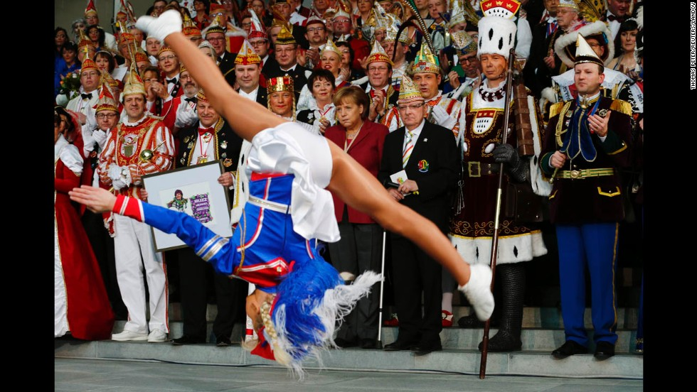 Liana Wolf performs as German Chancellor Angela Merkel, center, watches during a reception of German carnival societies at the Chancellery in Berlin on February 18.