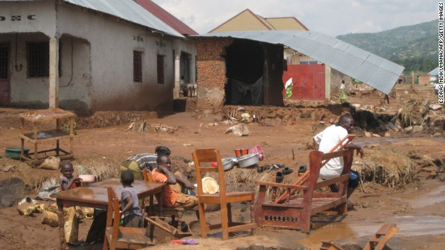 A familly sits outside their destroyed house, on February 11 in Bujumbura, after flooding and landslides caused by a night of torrential rain swept away hundreds of homes and killed at scores of people.