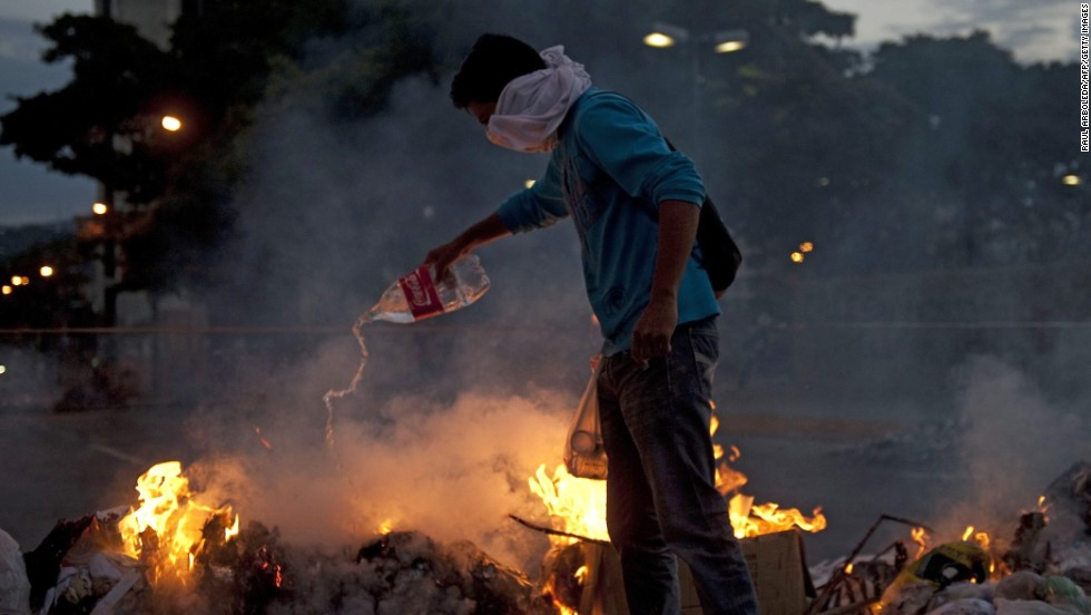 A protester adds fuel to a fire during clashes with police in Caracas on February 20.