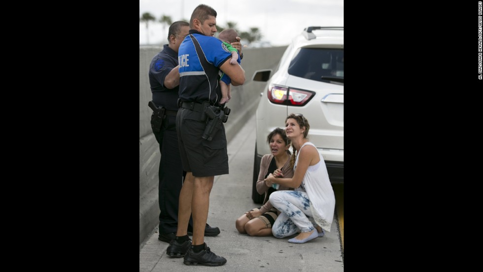 Police officer Amauris Bastidas holds the infant after responding to the scene. At the far right is Lucila Godoy, a woman who stopped her car to assist Rauseo.