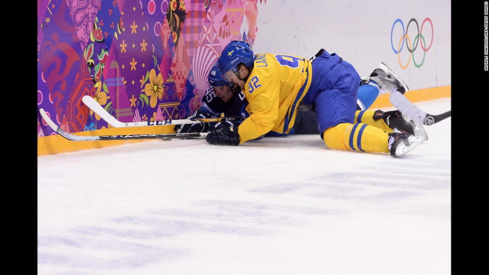 Finland's Sami Vatanen, left, vies for the puck with Sweden's Gabriel Landeskog during the men's hockey semifinal on February 21.