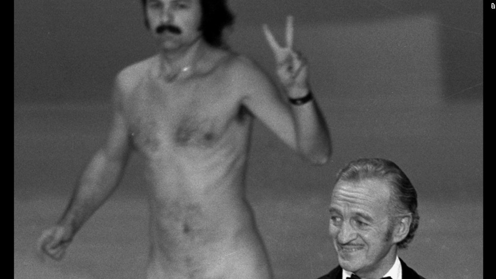 Oscar presenter David Niven isn't quite sure what's happening behind him as a streaker crosses the stage near the end of the 1974 Academy Awards. The streaker later identifies himself as Robert Opel.