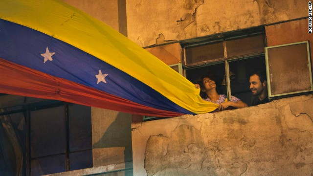 A woman waves a Venezuelan flag out her window on February 21 in Caracas.
