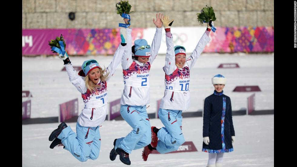 From left, second place medalist Therese Johaug, first place medalist Marit Bjoergen and third place medalist Kristin Stoermer Steira, all of Norway, celebrate during the flower ceremony for the 30-kilometer mass start free on Saturday, February 22.
