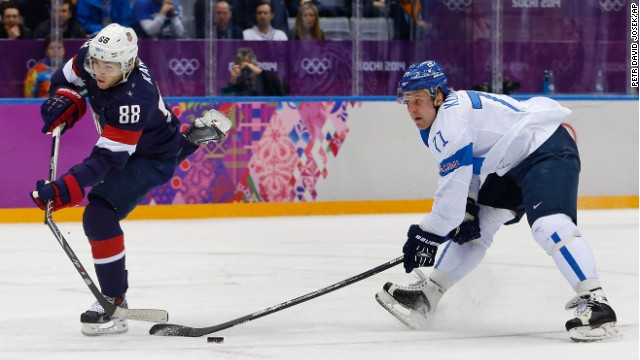 USA forward Patrick Kane breaks his stick while taking a shot on goal as Finland forward Leo Komarov defends Saturday.