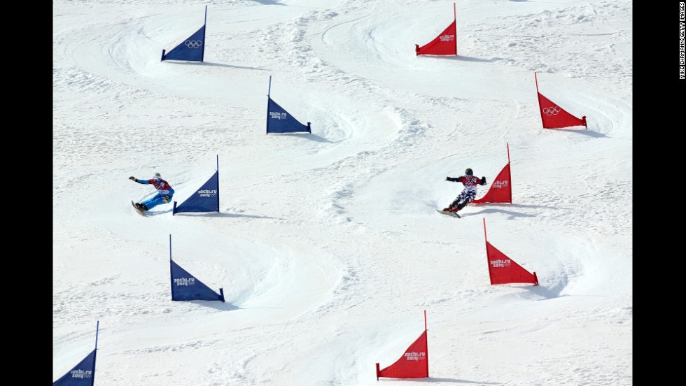 Vic Wild of Russia, right, and Benjamin Karl of Austria compete in the men's parallel slalom snowboard semifinals on February 22.