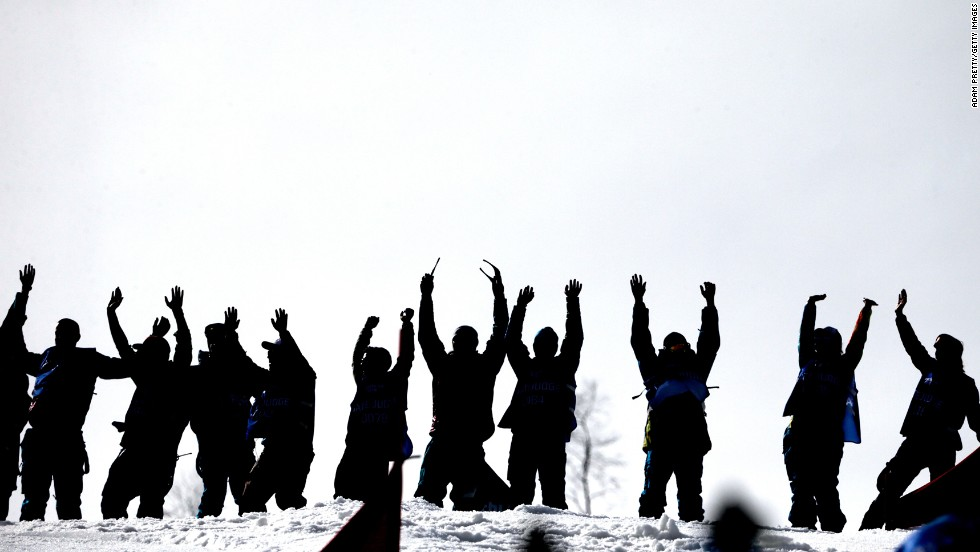 Venue staff celebrate on February 22 following the completion of the snowboard men's and ladies' parallel slalom finals.
