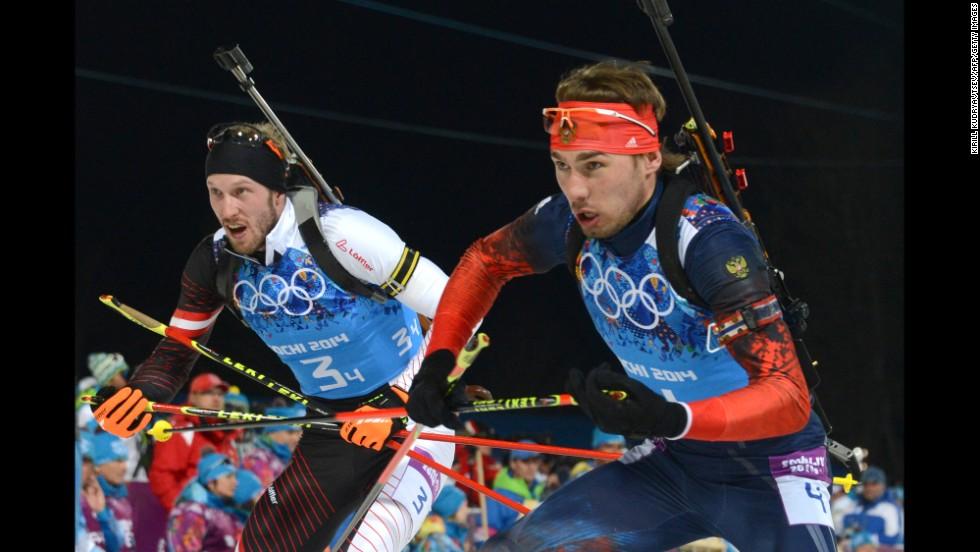 Austria's Dominik Landertinger, left, and Russia's Anton Shipulin leave the shooting range in the men's biathlon 4x7.5-kilometer relay on February 22.