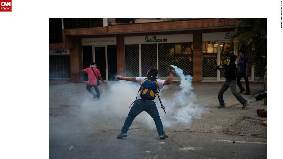 Manifestantes devuelven gases lacrimógenos a la policía.