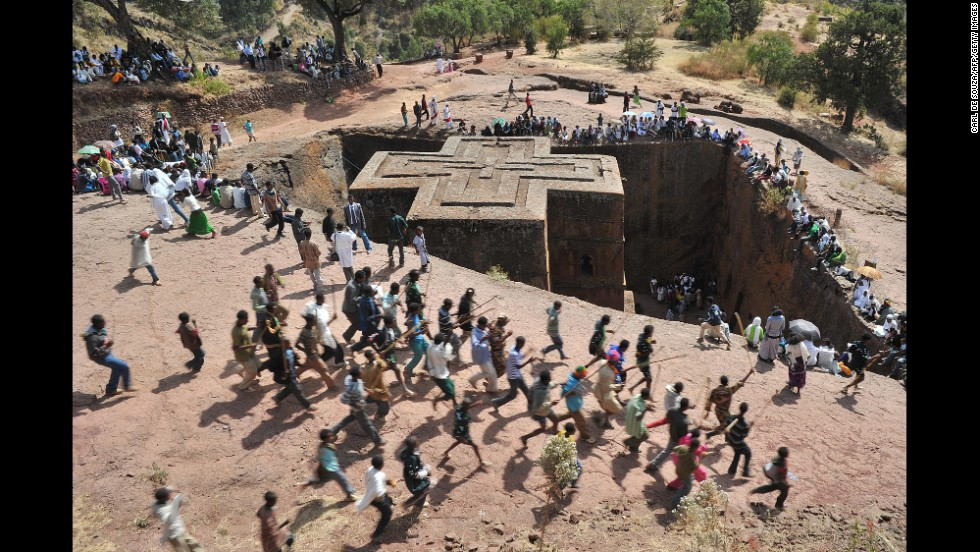Ethiopian Orthodox Christians dance near to the rock-hewn church Bete Giyorgis during the annual festival of Timkat in Lalibela, Ethiopia. Bete Giyorgis is one of the 13th century-era medieval, monolithic cave churches in Lalibela.