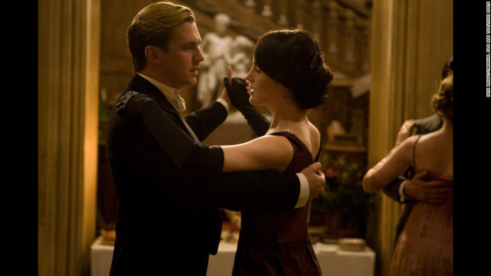 "Lady Mary Crawley dances with soon-to-be fiance Matthew. This elegant shot silk dress is on view in ""Costumes of Downton Abbey,"" an exhibition at Winterthur Museum, Garden and Library in Delaware. The engagement scene from the show is projected alongside the display of the dress and Matthew's evening wear."