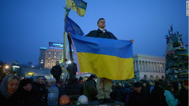 A man stands on a wall holding a Ukrainian flag while listening to speakers on stage in Independence Square on February 26, 2014 in Kiev, Ukraine.
