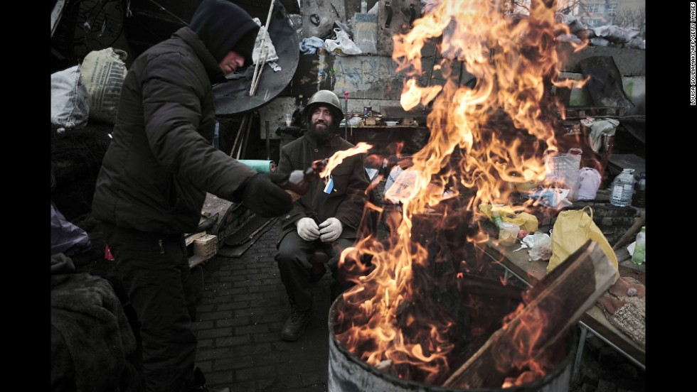 A man adds fuel to a fire at a barricade in Independence Square on February 27. Dozens of people were killed during clashes between security forces and protesters.