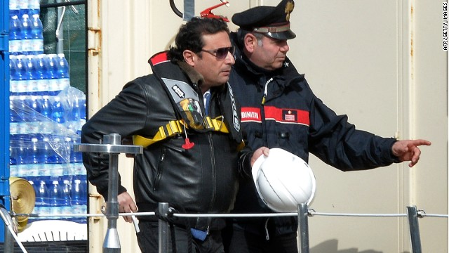 The captain of the wrecked Costa Concordia cruise ship Francesco Schettino (L) is escorted after he went onboard the wrecked Costa Concordia cruise ship in Giglio Port on February 27 , 2014.