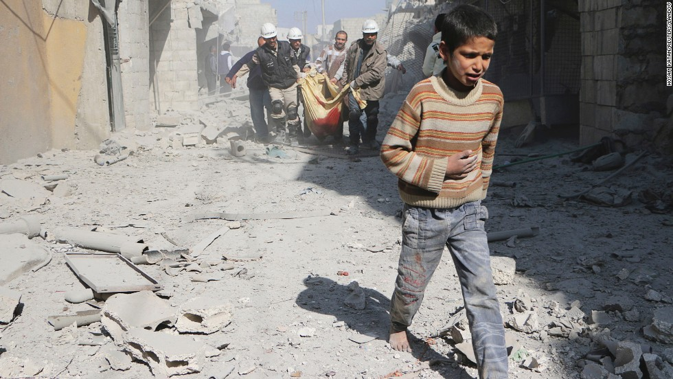 A boy walks ahead of men carrying the body of his mother in Aleppo on Saturday, February 22. According to activists, the woman was killed when explosive barrels were thrown by forces loyal to al-Assad.