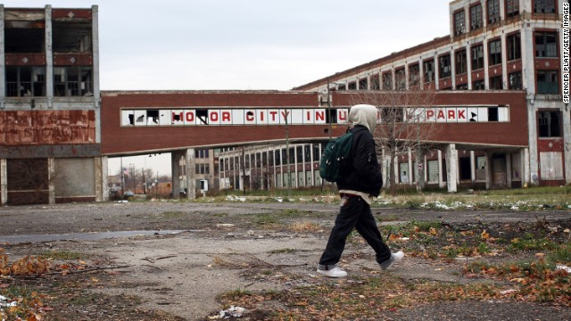 A person walks past the old Packard Motor Car Company in Detroit, which took a hit when its auto industry crumbled.