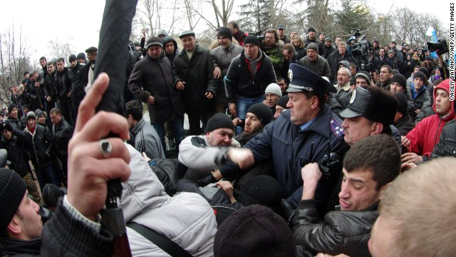 Ukrainian activists clash with pro-Russian activists as policemen try to separate in front of Crimean regional parliament in Simferopol on February 26, 2014. Pro-Russian demonstrators on Wednesday brawled with supporters of Ukraine's interim authorities in the capital of the Russophone Crimea region Simferopol, an AFP reporter at the scene said. Scuffles erupted as thousands of pro-Moscow residents and Muslim Crimean Tatars backing the new leadership in Kiev held competing rallies outside the regional parliament building, where local legislators rejected demands to debate splitting from Kiev. AFP PHOTO/ VASILIY BATANOV (Photo credit should read Vasiliy BATANOV/AFP/Getty Images)