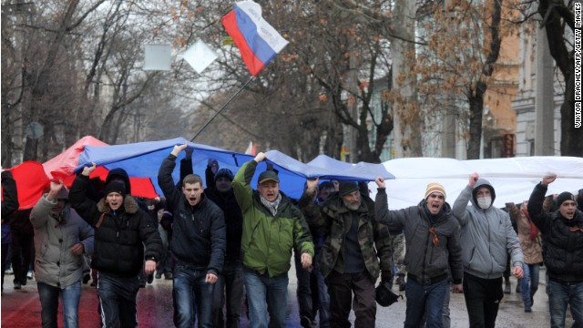 Pro-Russian demonstrators rally with a Russian flag raised above them in central Simferopol on February 27, 2014.