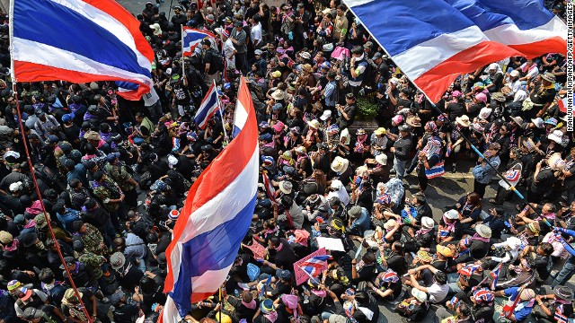 Travelers to Bangkok are advised to look up and avoid all potential protest sites. In this photo: Anti-government protesters wave Thai flags outside the national police headquarters on February 26.