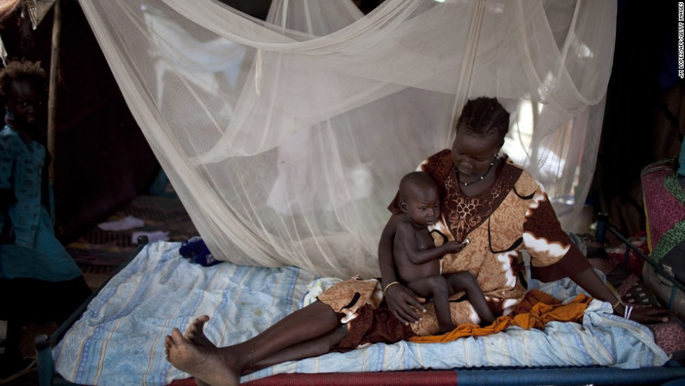 """A Nuer woman rests on a bed with her son in a camp for internally displaced people in Bor, South Sudan, on Thursday, February 27. <a href=""""http://www.cnn.com/2014/02/01/world/africa/south-sudan-aid-workers/index.html"""">Violence has quickly spread</a> throughout the country since rebels loyal to ousted Vice President Riek Machar tried to stage a coup in mid-December."""