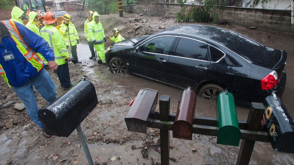 Workers try to help a woman get her car unstuck from the mud in Glendora on February 28.