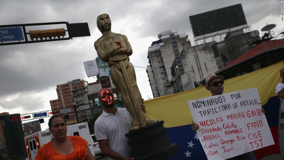 Un manifestante carga una estatua del Óscar durante una protesta contra el Gobierno.