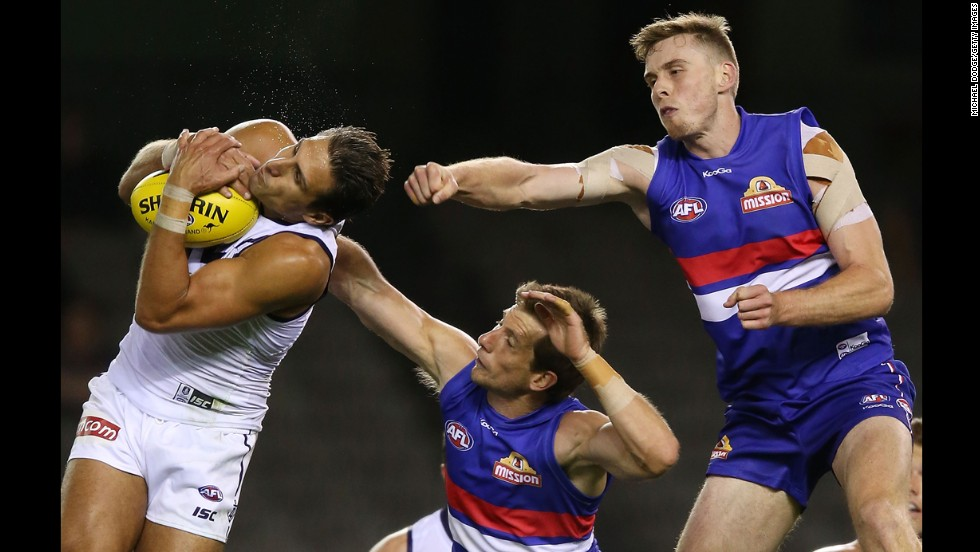 Matthew Pavlich of the Fremantle Dockers marks the ball against Jordan Roughead, right, and Dale Morris of the Western Bulldogs during an Australian rules football match Wednesday, February 26,  in Melbourne.