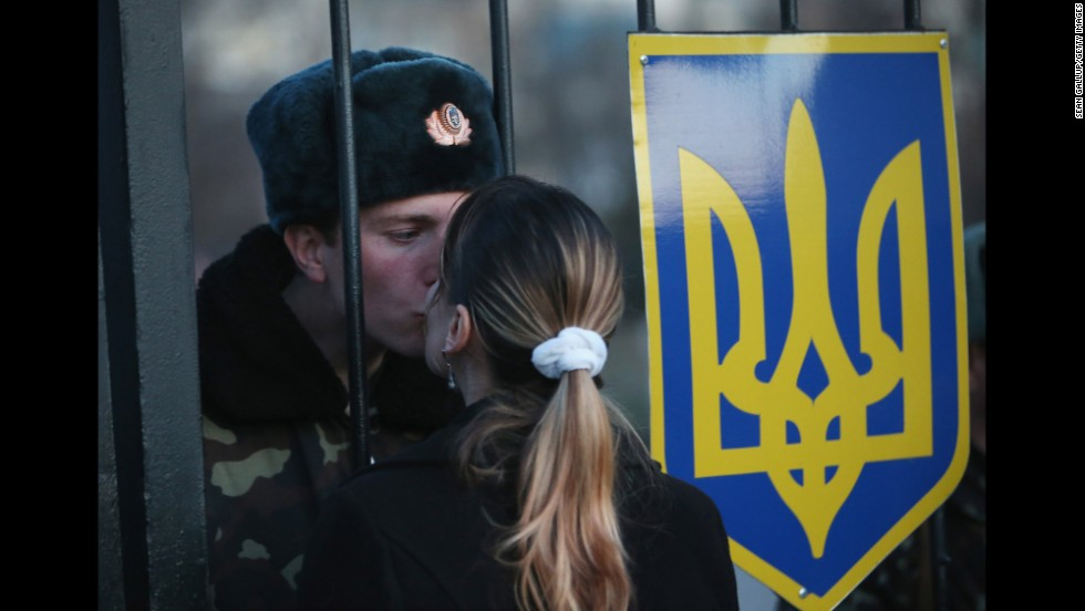 Oleg, a Ukrainian soldier, kisses his girlfriend, Svetlana, through the gates of the Belbek base entrance on March 3. Tensions are high at the base, where Ukrainian soldiers were standing guard inside the building while alleged Russian gunmen were standing guard outside the gates.
