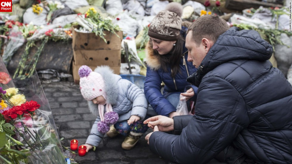 A young family lights candles in memory of those who died protesting in Maidan Nezalezhnosti, the central square of Kiev.