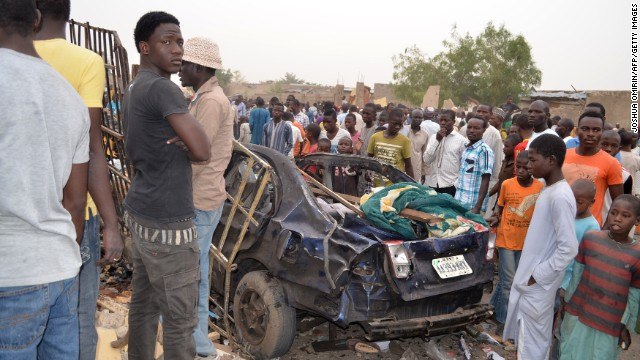 A crowd looks at the aftermath of an attack by suspected Islamist insurgents that killed 29 people in a northeast Nigerian village.