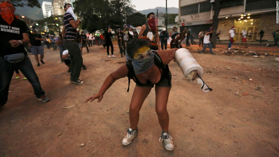 A protester ducks during clashes with police March 3 in Caracas.