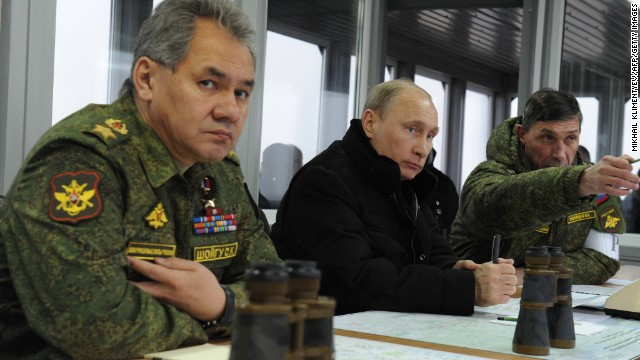 Russia's President Vladimir Putin (C) listens to the head of the Russian army's main department of combat preparation Ivan Buvaltsev (R) while watching military exercises at the Kirillovsky firing ground in the Leningrad region, on March 3, 2014, with  Defence Minister Sergei Shoigu (L)attending. Crimea, the strategic host to tsarist and Kremlin navies since the 18th century, has been under de facto occupation by Moscow-backed forces since Putin won recently parliament's authorisation to send troops into Ukraine. AFP PHOTO/ RIA-NOVOSTI/ POOL/ MIKHAIL KLIMENTYEV        (Photo credit should read MIKHAIL KLIMENTYEV/AFP/Getty Images)