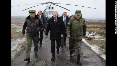 Russia's President Vladimir Putin and Defence Minister Sergei Shoigu walk to watch military exercises upon his arrival at the Kirillovsky firing ground in the Leningrad region, on March 3, 2014.