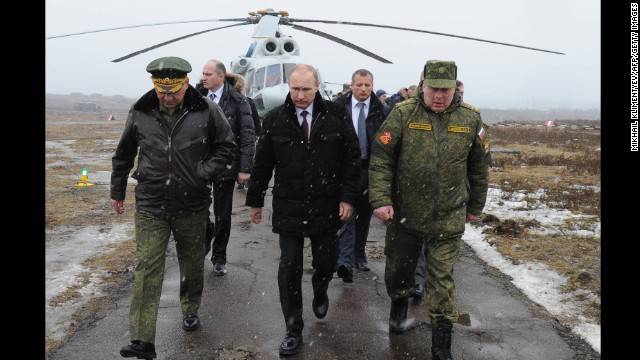 Russia's President Vladimir Putin, center, and Defense Minister Sergei Shoigu, left, arrives to watch a military exercise at the Kirillovsky firing ground in the Leningrad region, on March 3, 2014.